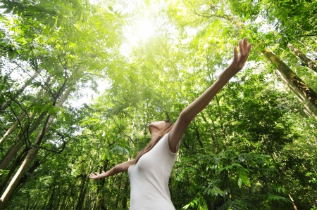 human energy: Young woman arms raised enjoying the fresh air in green forest