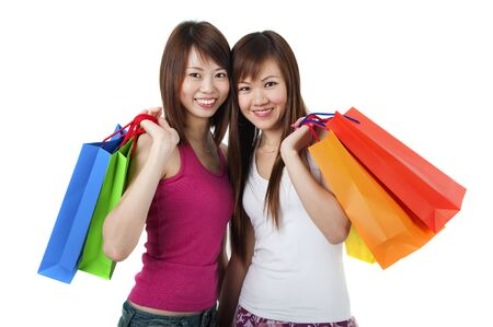 copysapce: Happy Asian girls standing with shopping bags against white background.