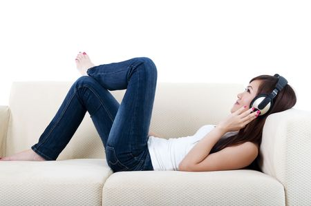 Young woman relaxing, listening to music, lying on sofa. Stock Photo