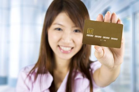 debit: Asian woman holding a credit card, focus on the card. Card number and expiry date created by my own.