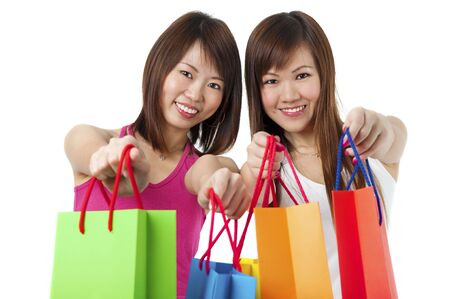 copysapce: Happy Asian girls showing their shopping bags against white background.