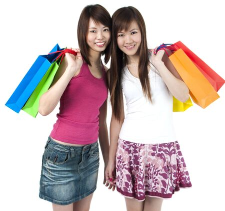 Happy Asian girls standing with shopping bags against white background. photo