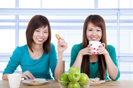 Two Asian women having tea break in home. photo