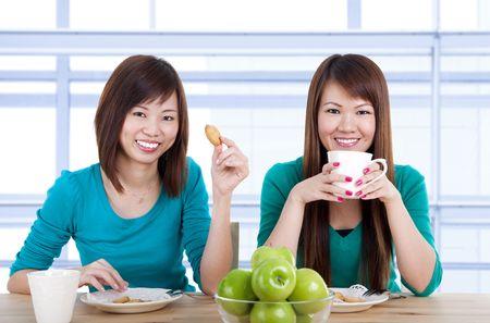 Two Asian women having tea break in home. photo