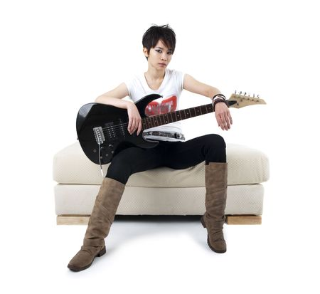 Punk Rockstar holding guitar sitting on sofa isolated in white photo