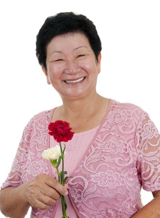 Happy Asian grandmother with carnation flowers on white background photo