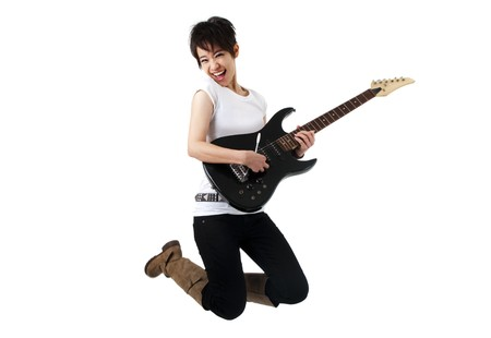 rocker: Asian female rockstar holding guitar jumping in air. Stock Photo