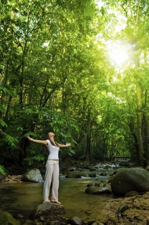 mujer meditando: Armas de mujer joven abrieron disfrutando del aire fresco en el bosque tropical de verde