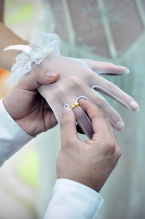 A groom is putting a wedding ring on brides hand photo
