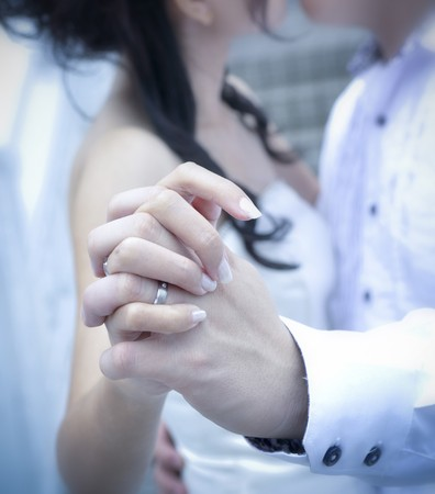 A bride and groom kissing on their wedding day, focus on hands photo