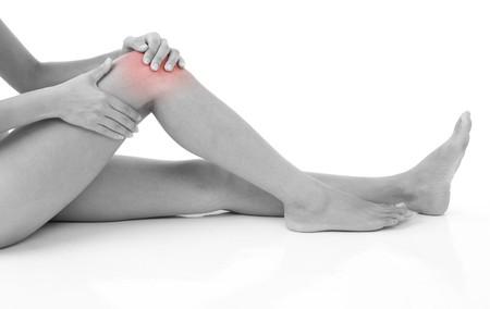 artrite: Woman holding sul ginocchio dolente isolato on white.