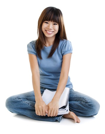 high school girl: Asian student sitting on floor, with cheerful expression.