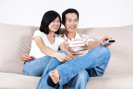 Asian couple sitting on sofa watching TV together. photo