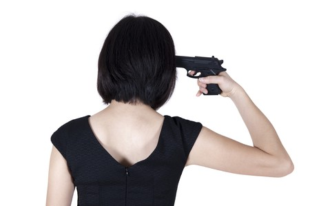 aiming: Woman with pistol pointing on her head, rear view isolated on white.