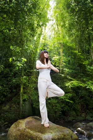 Female meditating in tropical rainforest, standing on a boulder. photo
