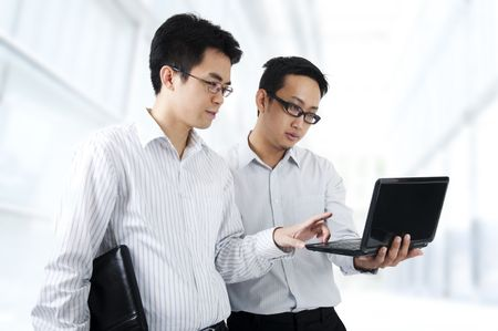 discussing: Two Asian young executives working on laptop, office building as background Stock Photo