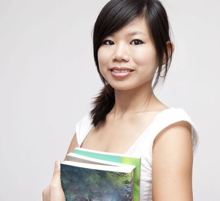 Portrait of young Asian woman with books photo