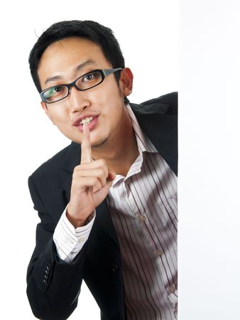 Asian man with blank board, finger on lips photo