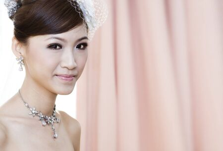 Beautiful Young Asian bride smiling, focus on foreground photo
