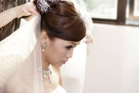 Asian bride having hairdo on her wedding day photo