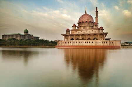 Putra Mosque is the principal mosque of Putrajaya, Malaysia. Building on the left is Perdana Putra which is Malaysian Prime Ministers office. Stock Photo