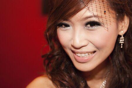 Beautiful Asian bride smiling, against red background 版權商用圖片