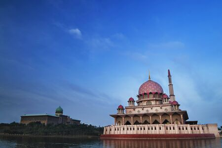 Stock Photo: Putra Mosque is the principal mosque of Putrajaya, Malaysia. Building on the left is Perdana Putra which is Malaysian Prime Ministers office. photo
