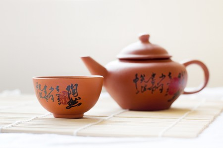 chinese script: Chinese ceramic teapot and cups. The Chinese word on the pot is a poem. Stock Photo