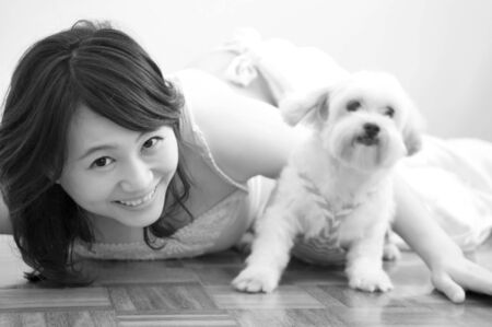 Asian woman playing with her pet, black and white. photo