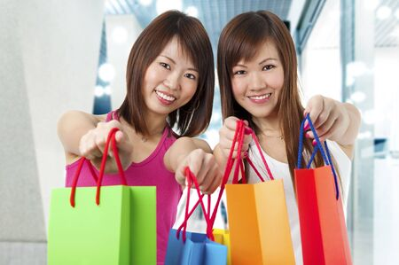 shopping centre: Happy Asian girls standing with shopping bags, shopping mall as background. Stock Photo