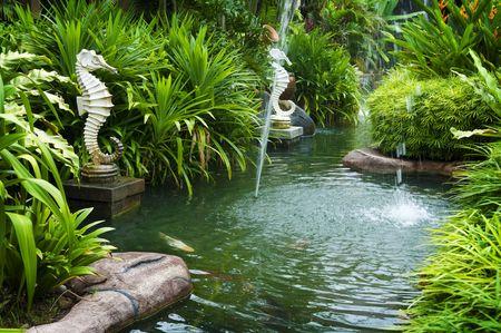 Tropische zen uitzicht op de tuin met fontein en groene planten. Stockfoto