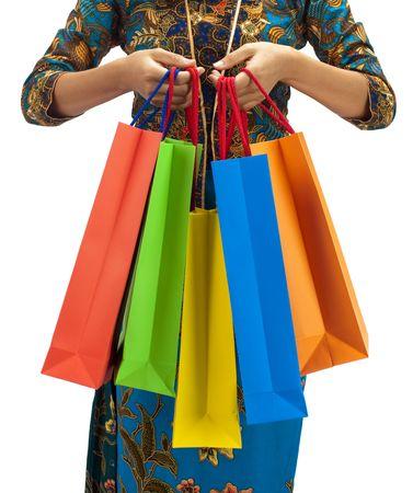 Woman in tradition Kebaya holding colorful shopping bag.
