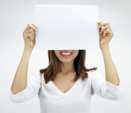 covering eyes: Concept photo of Asian woman holding a white card, covering her eyes.