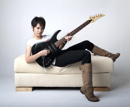 Punk Rockstar holding a guitar sitting on sofa. photo