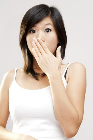 Shocked woman covering her mouth by hand. photo