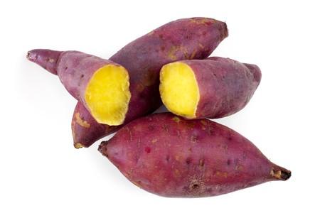 batata: Cocinadas enteras y mitad batatas sobre fondo blanco.