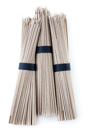 soba noodles: Bundles of raw buckwheat soba noodles. Isolated on white.