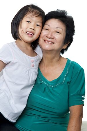 Photo of Asian grandmother and granddaughter on white background. photo