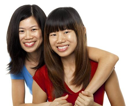 Two Asian sisters isolated on white background photo
