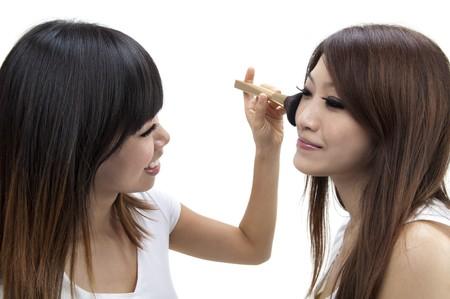 Femme asiatique appliquant make up, isolé sur fond blanc