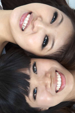 Closeup portrait of happy young girls lying on ground with their heads together  photo