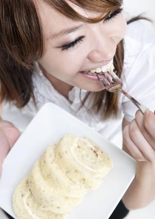 Young Asian woman is enjoying cake rolls photo