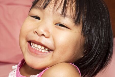 3 4 years: Close-up shot of a young Asian girl with smile on her face. Stock Photo