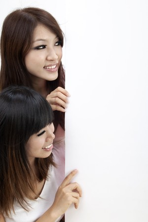 Two attractive young asian women looking at a verical blank sign photo