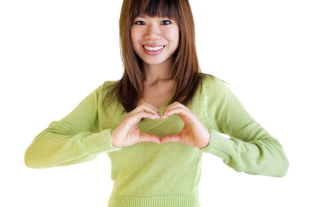 forming: A womans hands forming a heart symbol on chest