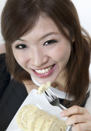Young woman enjoying cake rolls, looking up. photo