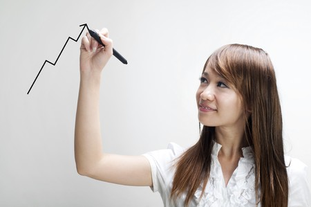 Closeup of young Asian business woman drawing graph on transparent glass or foil. photo