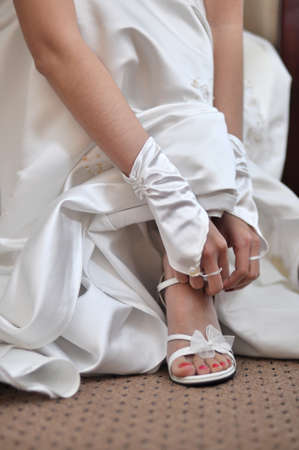 dressing up: Bride is putting on her wedding shoes