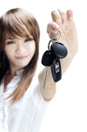 Young woman holding her first own car key on white background, focus on car key. photo