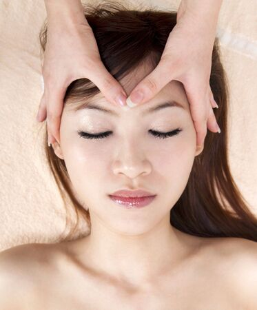 Beauty and Spa - Asian Girl having a massage on her head photo